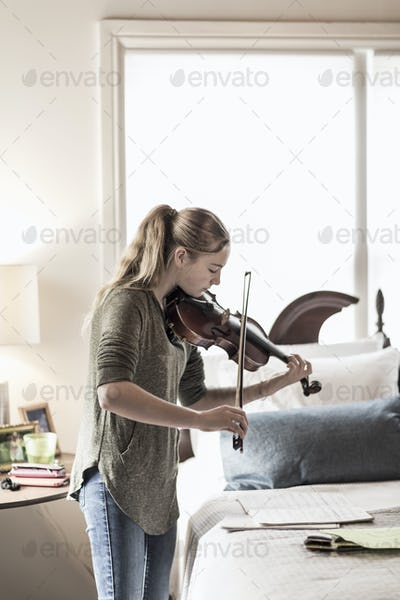 13 year old girl playing violin in bedroom