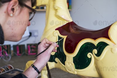 Close up of woman in workshop, painting traditional wooden carousel horse from merry-go-round.