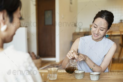Two Japanese women sitting at a table in a vegetarian cafe, pouring tea.
