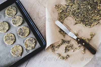 High angle close up of seeded cracker dough on a baking tray.