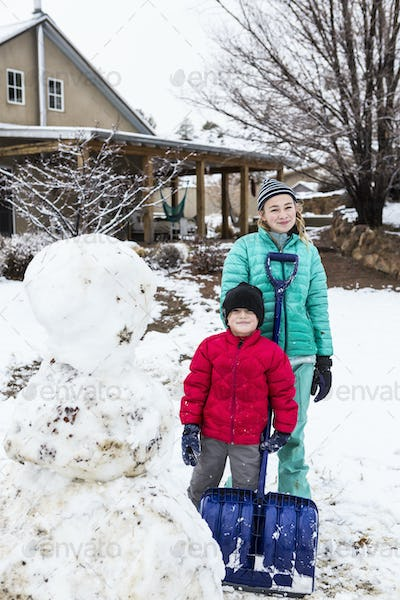 portrait of Thirteen year old teenage girl and her 6 year old brother posing with snowman