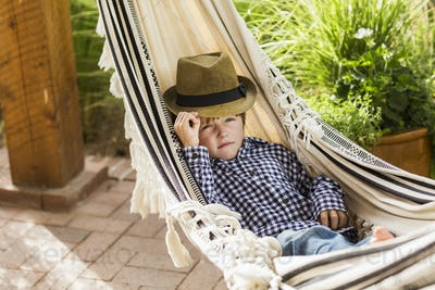 portrait of 6 year old boy lying in hammock on porch
