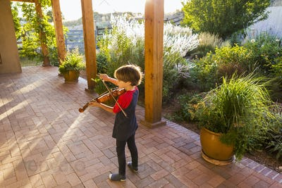 6 year old boy playing violin outside in garden