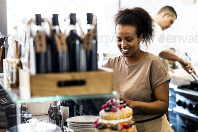 A woman working in a cafe, a stack of plates, and a layered sponge cake with fresh cream and fresh