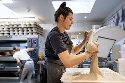 Woman wearing apron standing in an artisan bakery, working with sourdough.