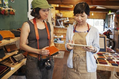 Two Japanese women standing in a leather shop, holding leather purse and digital tablet.