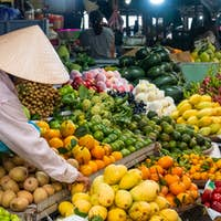 Vendor at his fruit and vegetable stall at a market in Hoi An, Vietnam.