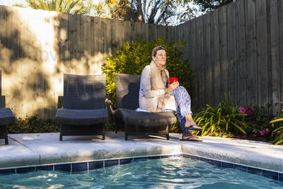 Woman sitting on sun lounger by a swimming pool