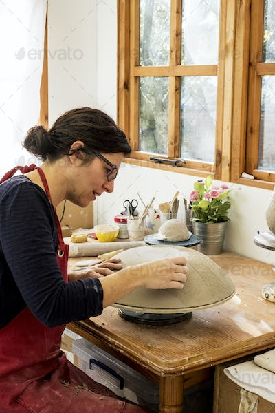 Woman wearing red apron sitting in her ceramics workshop, working on clay bowl.