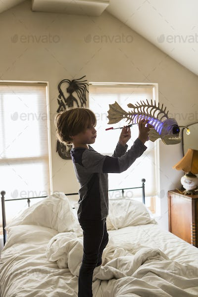 6 year old boy playing with his toys on his bed