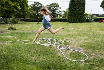 Girl wearing denim dungarees jumping over a garden hose on a lawn.