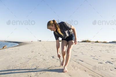 A teenage girl playing in sand dunes, at the beach