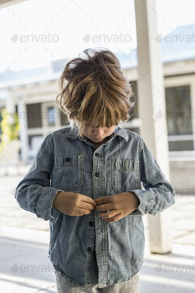 6 year old boy buttoning up his denim shirt