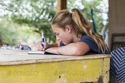 13 year old girl reading and writing in her diary