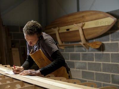 Paddleboard maker using mobile phone in workshop