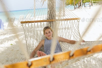 13 year old girl relaxing in a hammock on the beach