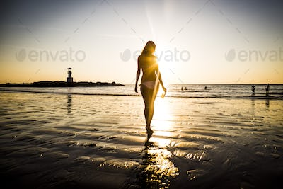 Rear view of woman walking toward the beach during sunset.