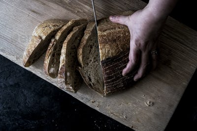 A hand holding a loaf of bread and using a breadknife to cut slces.
