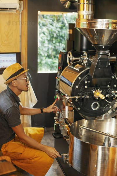 Japanese man wearing hat and glasses sitting in an Eco Cafe, operating coffee roaster machine.