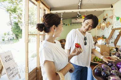 Two smiling Japanese women looking at fresh vegetables in a farm shop.
