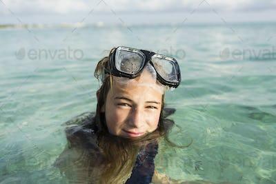 13 year old girl wearing snorkeling mask in the ocean