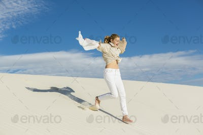 13 year old girl leaping and dancing in light white sand sand in a dunes landscape.