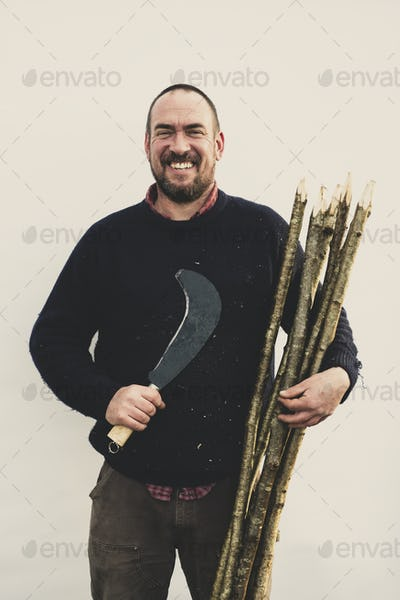 Bearded man holding bill hook and bunch of wooden stakes for traditional hedge laying, smiling at