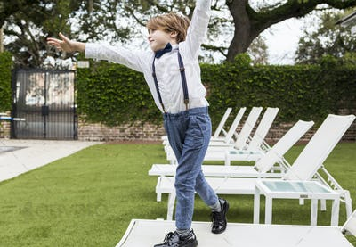 6 year old boy standing on lawn chair