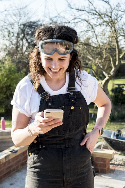 Smiling woman wearing dungarees and protective goggles checking her mobile phone.