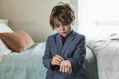 6 year old boy adjusting his watch band