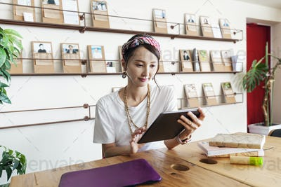 Female Japanese professional sitting at table in a co-working space, using digital tablet and