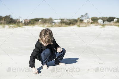A six year old boy drawing in the soft white sand on the beach