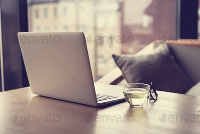 Freelance Desk with open laptop, cup of green tea and glasses on table