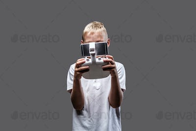 Blonde boy posing in a dark studio.
