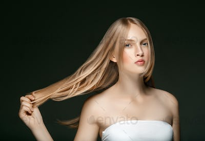 Young girl face beauty skin portrait with long blonde hair with hand over dark background