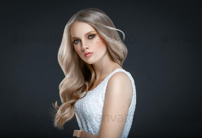 Adult beautiful girl with long wavy hair. Blonde model with hairstyle over black background