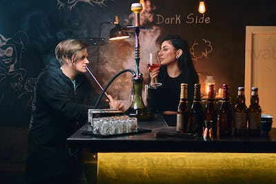 Seductive brunette woman and handsome guy in hoodie smokes a hookah