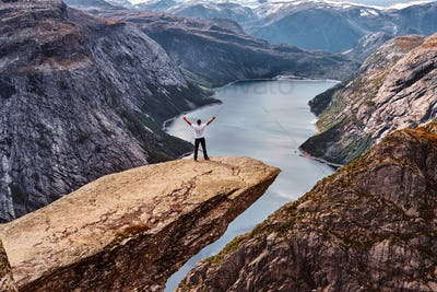 Tourist man standing in the Trolltunga and enjoys a beautiful view of the Norwegian fjord.