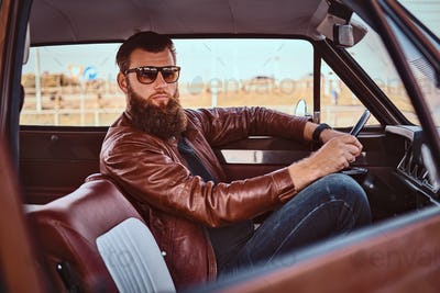 Bearded male in sunglasses dressed in brown leather jacket driving a retro car.