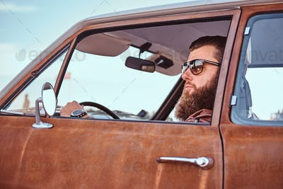 Bearded male dressed in brown leather jacket and boots with tuned retro car