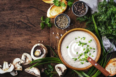 Creamy Mushroom Soup with croutons and chives on rustic wooden background