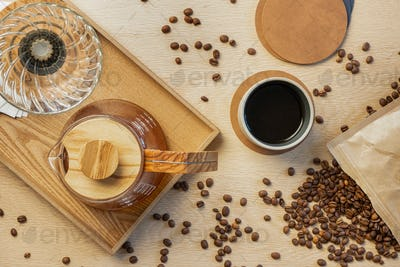 Directly above shot of fresh coffee with roasted beans on wooden table