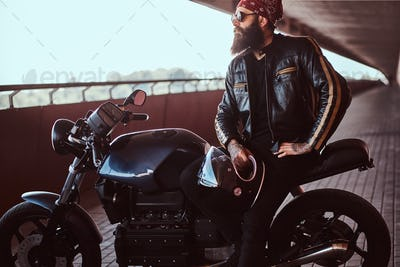 Stylish bearded male dressed in a black leather jacket sitting on his custom-made retro motorcycle