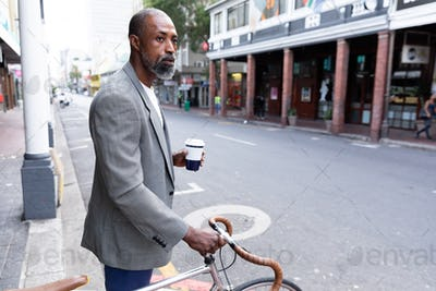 African American man riding a bike in the city street