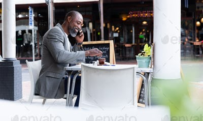 African American man spending time at a coffee terrace