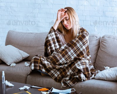 Woman feeling cold, covered blanket and touches forehead