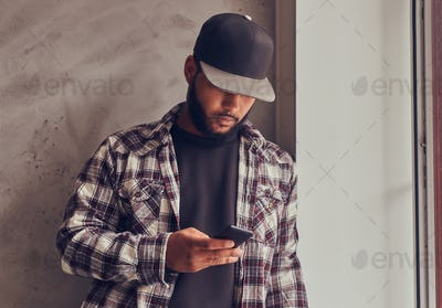 African-American bearded man chatting in the social network while standing next gray textured wall.