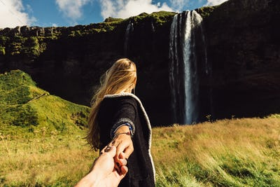 cropped shot of girl holding hand of friend and going to majestic waterfall in Iceland