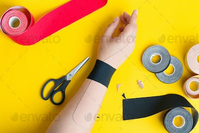 Woman's hand with application from colored tapes on a yellow background and special physio
