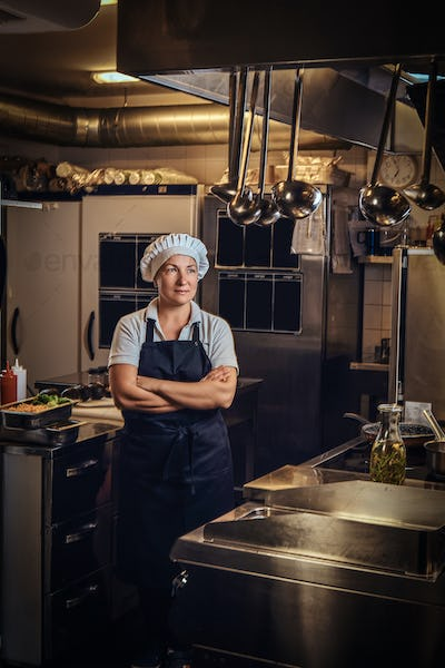 A middle age cook wearing a uniform standing with her arms crossed at restaurant's kitchen.
